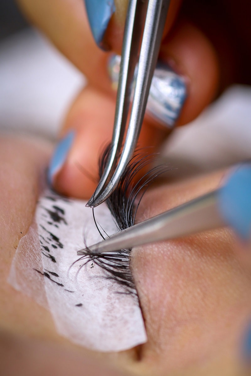 close-up of woman's eye undergoing a lash extension procedure