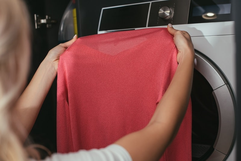 cropped view of housewife holding pullover near washing machine