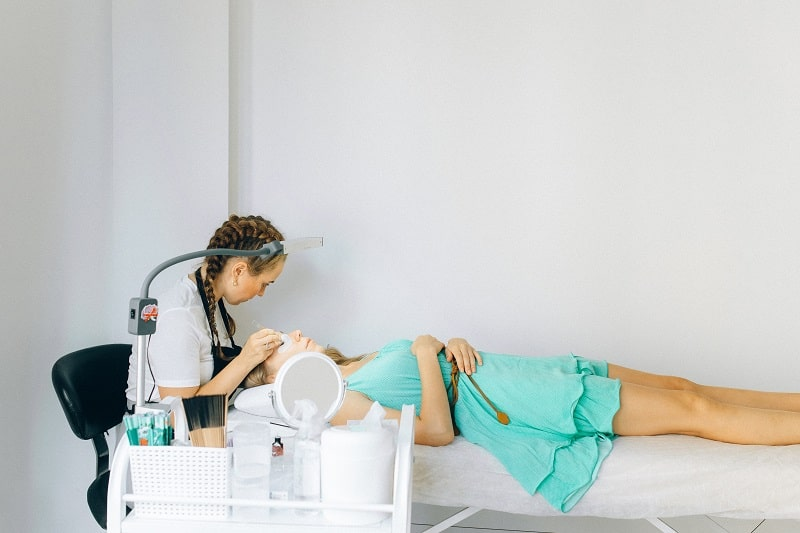 woman lying on a lash bed getting eyelash extensions done