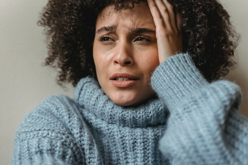 attractive black woman wearing false eyelashes crying in despair holding her head with left hand
